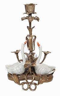 Подсвечник Лебеди. Бронза, керамика. Вторая половина ХХ векаПКППМППодсвечник Лебеди. Бронза, керамика. Западная Европа, вторая половина ХХ века. Размер 16 х 16 х 30 см. Сохранность хорошая. Без клейма. На металлической подставке подсвечника создана композиция из цветов, в центральном из которых расположена чаша подсвечника. К нему тянут свои головки три белых лебедя, их фигурки выполнены из керамики. Изделие смотрится целостным и гармоничным, его оформление - нежным и легким.