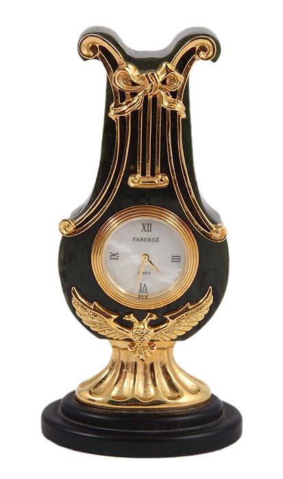 Часы настольные Лира. Зеленый оникс, лабрадор, перламутр, позолота, швейцарский кварцевый механизм, House of Faberge, 1980-1990-е ггАККААИдеально для роскошного представительского подарка высокопоставленному лицу! Часы настольные Лира. Зеленый оникс, лабрадор, перламутр, позолота, швейцарский кварцевый механизм. Западная Европа, 1980-1990-е гг. Высота 12 см, ширина 5 см. Сохранность очень хорошая. На часовом циферблате клеймо дома Фаберже. На основании - тисненое клеймо Faberge. Часы хранятся в оригинальной коробке с фирменным логотипом Faberge и сопровождаются сертификатом подлинности фирмы Фаберже. Великолепные настольные часы Лира из зеленого оникса гармонично сочетают красоту материалов, филигранную работу художников и классический стиль Фаберже! Центральный элемент декора - рельефное изображение орла с широко расправленными крыльями - символ ювелирного дома и герб Российской Империи. Часы выполнены в форме лиры, которая традиционно является олицетворением гармонии, творческого вдохновения, поэзии, искусства и...