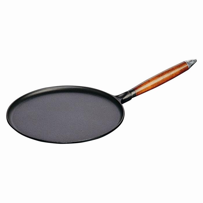 Сковорода для блинов Staub 28см, 12128231212823Сковорода Staub изготовлена из чугуна и покрыта эмалью снаружи и внутри. Она имеет очень низкие бортики, что делает ее удобной для приготовления блинов и оладьев. Особая форма бортиков позволяет легко перевернуть блюдо и облегчает сервировку. Высокая теплоемкость чугуна позволяет ему сильно нагреваться и медленно остывать, а это в свою очередь обеспечивает равномерное приготовление продуктов. Пища, приготовленная в чугунной посуде, сохраняет свои вкусовые качества, и благодаря экологической чистоте материала, не может нанести вред здоровью человека. Также чугунная сковорода обладает высокой прочностью и износоустойчивостью. Сковорода оснащена удобной деревянной ручкой, которая дает возможность забыть о прихватках, но и накладывает ограничения на использование посуды в духовке. Также в комплект входят деревянная лопатка и приспособление для распределения теста по поверхности сковороды. Сковорода Staub подходит для использования на всех типах кухонных плит. ...