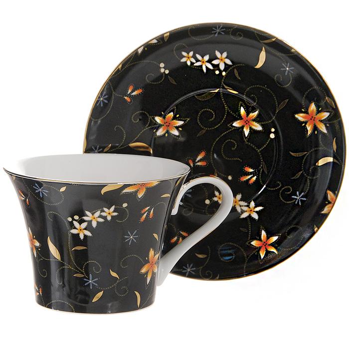 Чайная пара Diademine. 1111114601137103938Чайная пара Diademine, состоящая из чашки и блюдца, доставит истинное удовольствие ценителям прекрасного. Предметы набора изготовлены из высококачественного фарфора и имеют оригинальную форму. Они оформлены красочным цветочным узором на черном фоне, который придает изделиям особый шарм. Чайная пара Diademine сочетает в себе изысканный дизайн с максимальной функциональностью. Изысканное оформление придется по вкусу и ценителям классики, и тем, кто предпочитает утонченность и изящность. Такой набор станет отличным подарком на любой праздник. Предметы упакованы в стильную подарочную коробку из плотного картона яркого оранжевого цвета.
