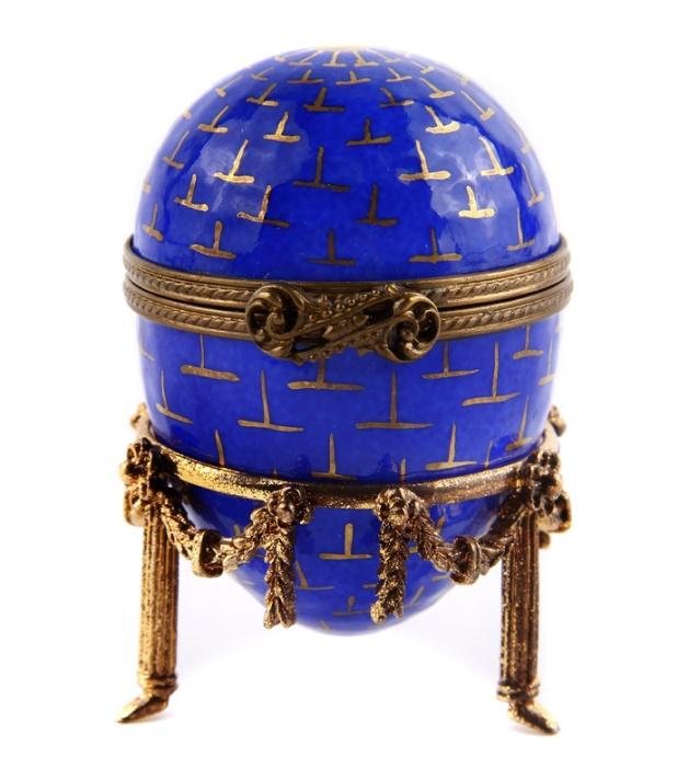 Яйцо Часы. Металл, эмаль, House of Faberge, 1990-е гг.АККААЯйцо Часы. Металл, эмаль. Западная Европа, Фаберже, 1990-е гг. Высота 9,5 см, диаметр 4 см. Сохранность хорошая. На дне верхней крышки от руки Faberge. Peint Main. Limoges France. Синее яйцо установлено на подставке в виде трех золоченых колонн, соединенные между собой растительными венками. Классический циферблат часов расположен на горизонтальной вкладке, окружен рельефным узорчатым орнаментом. Защелкой служит изящный изогнутый завиток.