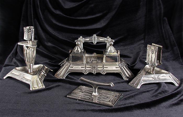 Письменный гарнитур из 4-х предметов Венский (набор письменных принадлежностей). Металл, серебрение, чернение, выколотка, фарфор. Австрия, около 1895 годаАОКАРГКИдеально для представительского подарка высокопоставленному лицу! Письменный гарнитур из 4-х предметов Венский (набор письменных принадлежностей). Металл, серебрение, чернение, выколотка, фарфор. Австрия, около 1895 года. Набор составили: чернильница, подсвечник, подставка для бумаг и визиток, подставка для пера или ручки. Размеры: Чернильница: 26 х 15,5 х 10,5 см; Подставка для бумаг: размер основания 15 х 16,5 см, высота 10,5 см; Подставка для пера: размер основания 13 х 7,5 см; Подсвечник: высота 16 см, размер основания 15 х 16,5 см, диаметр розетки 2,2 см. Сохранность коллекционная. На основаниях предметов клейма Gesetzlich Geschutzt и номера 1745, 1746-1747. Конструкция чернильницы предусматривает 2 емкости для чернил. Роскошный письменный гарнитур в стиле модерн станет изысканным акцентом интерьера Вашего кабинета! Безупречное исполнение, изысканный стиль, особенности декора и утонченные линии...