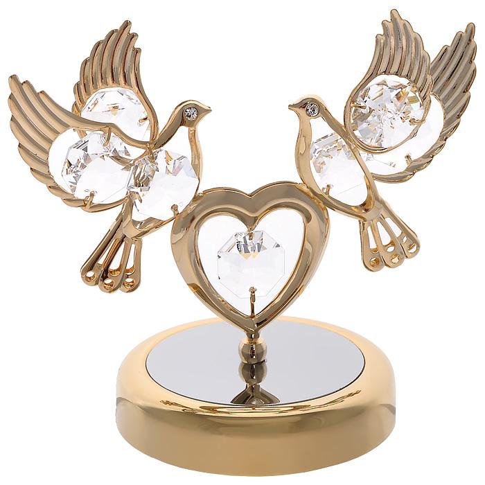Фигурка декоративная Голуби с сердцем, цвет: золотистый67093Декоративная фигурка Голуби с сердцем, золотистого цвета, станет необычным аксессуаром для вашего интерьера и создаст незабываемую атмосферу. Фигурка выполнена в виде двух голубей, сидящих на сердце, и декорирована прозрачными кристаллами. Кристаллы, украшающие фигурку, носят громкое имя Swarovski. Ограненные, как бриллианты, кристаллы блистают сотнями тысяч различных оттенков. Эта очаровательная вещь послужит отличным подарком близкому человеку, родственнику или другу, а также подарит приятные мгновения и окунет вас в лучшие воспоминания. Фигурка упакована в подарочную коробку. Характеристики: Материал: металл (углеродистая сталь, покрытие золотом 0,05 микрон), австрийские кристаллы. Размер фигурки: 9 см х 8,5 см х 6 см. Цвет: золотистый. Размер упаковки: 9 см х 10 см х 6,5 см. Артикул: 67093. Более чем 30 лет назад компания Crystocraft выросла из ведущего производителя в перспективную торговую марку, которая задает...