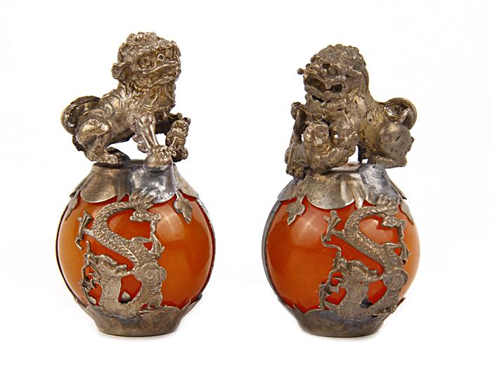 Настольный декор Львы-стражи. Металл, оранжевый жадеит. Китай, 1980 год52134Настольный декор Львы-стражи. Металл, оранжевый жадеит. Китай, 1980 год. Сохранность хорошая. Размер 3,5 х 6 см. Львы-стражи располагаются парой по обеим сторонам входа. При этом, по правую руку обычно располагается лев, по левую — львица. Лев придерживает лапой шар, который в буддийской традиции трактуется как тема — сокровище, символ буддийского знания, несущий свет во тьму и могущий исполнять желания. Львица придерживает лапой львёнка. Одна фигура с открытой пастью, другая — с закрытой. Это трактуется по-разному: как символ рождения и смерти; как символ открытости к добрым помыслам и неприятия злых. Открытая пасть должна отпугивать злых демонов, закрытая — удерживать и защищать добрых.