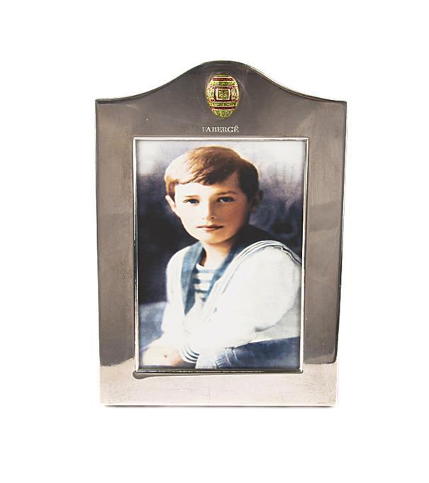 Фоторамка настольная. Белый металл, эмаль гильош, House of Faberge, 1990-е гг.15947Фоторамка настольная. Белый металл, эмаль гильош. Западная Европа, Фаберже, 1990-е гг. Размер рамки 12 х 17 см; размер окна 8 х 11,5 см. Сохранность очень хорошая. Тисненое клеймо Faberge. Имеется ножка для подставки. Рамка хранится в оригинальном футляре, украшенном тисненым гербом с изображением двуглавого орла. Размер футляра 20 х 25 х 5 см. Стильная настольная рамка Faberge станет особенным акцентом в интерьере Вашего рабочего кабинета или гостиной, подчеркнет статус и безупречный вкус! Рамка выполнена из белого металла и украшена миниатюрным изображением яйца Фаберже - традиционного символа марки. Минималистичный декор, стильная и лаконичная форма придают изделию особенный шик и подчеркивают благородство! Роскошный предмет интерьера, который станет великолепным подарком ценителю редких и изысканных вещей!