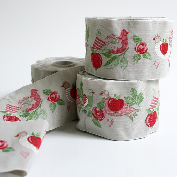 Тесьма декоративная Яблоки и голуби, цвет: серый, красный, 1 м х 50 мм. 35066-0335066-03Изысканная декоративная тесьма Яблоки и голуби выполнена из высококачественного 100% полиэстера. На ленте изображены голуби, яблоки, сердца, цветы и листья. Рисунок выполнен из 100% хлопка. Тесьма Acufactum ткется на старинных станках с использованием перфокарт, которые изготавливаются для каждого вида тесьмы с тончайшей проработкой самых мелких деталей. Это достаточно долгий и трудоемкий процесс, но результат того стоит! Тесьма наивысшего уровня качества, которая очень практична в использовании т.к. выдерживает стирку при температуре 60 градусов. А изобилие дизайнов просто потрясает!