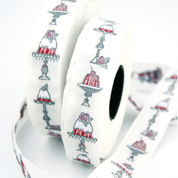 Тесьма декоративная Пирожные, цвет: белый, серый, красный, 1 м х 20 мм. 35108-0235108-02Изысканная декоративная тесьма Пирожные выполнена из высококачественного 100% полиэстера. На ленте изображены разнообразные пирожные. Рисунок выполнен из 100% хлопка. Тесьма Acufactum ткется на старинных станках с использованием перфокарт, которые изготавливаются для каждого вида тесьмы с тончайшей проработкой самых мелких деталей. Это достаточно долгий и трудоемкий процесс, но результат того стоит! Тесьма наивысшего уровня качества, которая очень практична в использовании т.к. выдерживает стирку при температуре 60 градусов. А изобилие дизайнов просто потрясает!