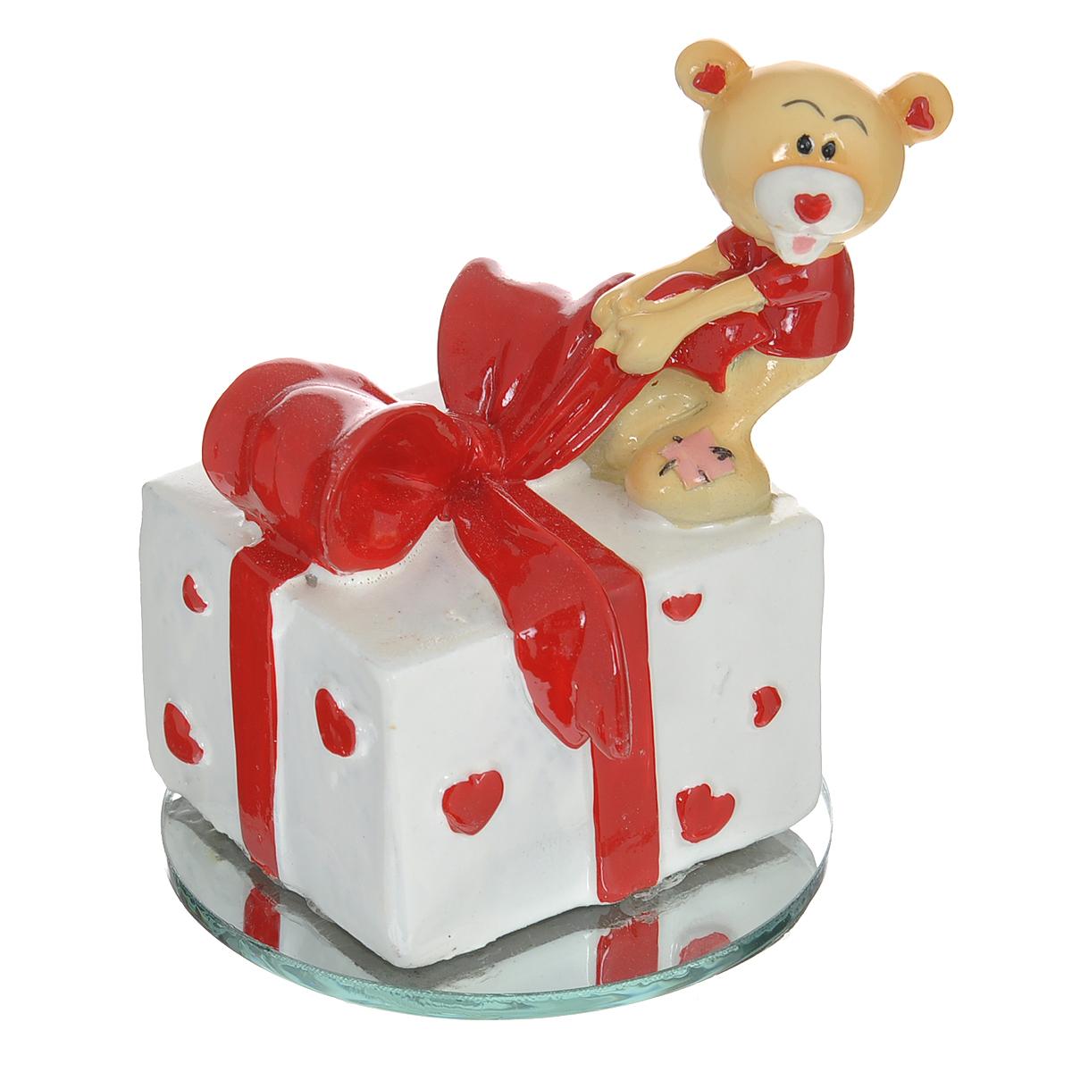 Фигурка декоративная Мишка-валентинка. 123435123435Декоративная фигурка Мишка-валентинка изготовлена из полистоуна в виде милого медвежонка, открывающего подарок. Фигурка расположена на круглой зеркальной подставке. Такая фигурка станет идеальным сувениром ко Дню Святого Валентина, она без лишних слов выразит все ваши чувства. Фигурка упакована в подарочную коробку, перевязанную красной атласной лентой. Характеристики: Материал: полистоун, стекло. Цвет: бежевый, красный, белый. Диаметр основания: 6,5 см. Высота фигурки: 8 см. Размер упаковки: 9,5 см х 9 см х 11 см. Артикул: 123435.