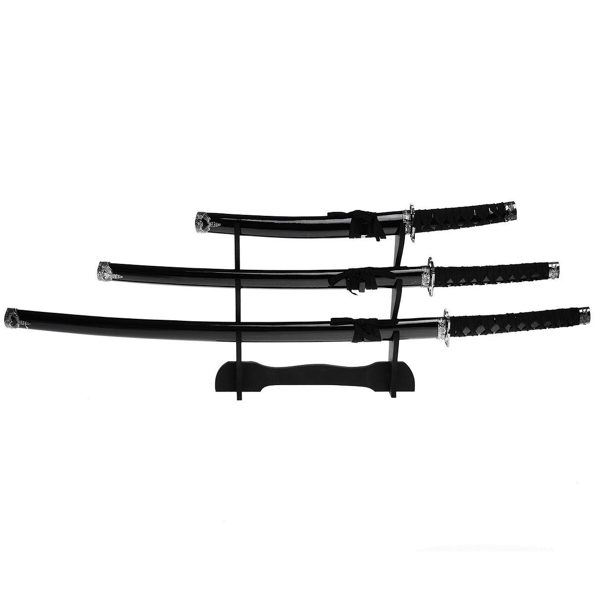 Набор самурайских мечей на подставке, 3 шт. 454263454263Самурайский меч соединяет в себе духовный и материальный миры, физическое и духовное начало... Набор самурайских мечей состоит из длинного меча - катаны, среднего - вакидзаси и короткого меча - танто. Изготовлены они в традиционном японском стиле из стали, ножны украшены плетением из текстильного шнурка. Этот набор - изысканный подарок поклонникам культуры Востока и прекрасное дополнение интерьера вашей квартиры или офиса. В качестве настенного украшения самурайские мечи использовались еще с древности, знаменуя собой подвиги славных предков. Благодаря специальной подставке, вы можете не только повесить мечи на стену, но и поставить в любое удобное для вас место. Характеристики: Материал: металл, пластик, дерево, текстиль. Длина мечей: 100 см; 81 см; 54 см.