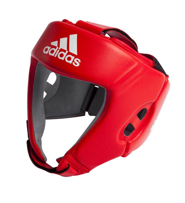 Шлем боксерский Adidas AIBA, цвет: красный. AIBAH1. Размер S (44-48 см)AIBAH1Боксерский шлем Adidas AIBA разработан и спроектирован для обеспечения максимальной защиты и оптимальной видимости. Шлем сертифицирован Международной ассоциацией бокса (AIBA). Оболочка шлема изготовлена из натуральной кожи, что увеличивает срок эксплуатации шлема. Внутреннее наполнение из пены, изготовленной по технологии Air Cushion, обеспечивает отличную амортизацию ударных нагрузок. Внутренняя подкладка выполнена из высокотехнологичной, искусственной кожи Amara. Шлем имеет легкую конструкцию без защиты скул. Два широких ремня фиксируемых липучкой на теменной части и два ремня на липучке в затылочной части позволяют регулировать размер шлема и обеспечивают плотную и удобную посадку, исключая смещение шлема во время боя. Так же шлем имеет регулируемый ремешок под подбородком.