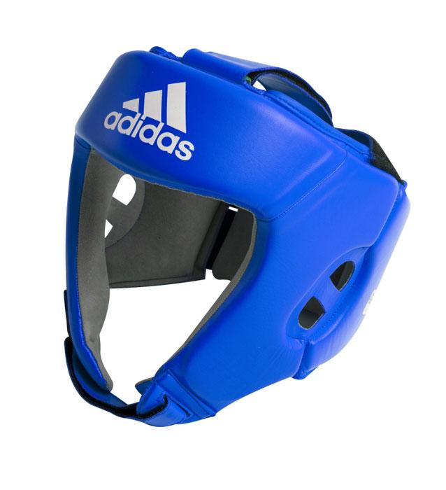 Шлем боксерский Adidas AIBA, цвет: синий. AIBAH1. Размер L (52-56 см)AIBAH1Боксерский шлем Adidas AIBA разработан и спроектирован для обеспечения максимальной защиты и оптимальной видимости. Шлем сертифицирован Международной ассоциацией бокса (AIBA). Оболочка шлема изготовлена из натуральной кожи, что увеличивает срок эксплуатации шлема. Внутреннее наполнение из пены, изготовленной по технологии Air Cushion, обеспечивает отличную амортизацию ударных нагрузок. Внутренняя подкладка выполнена из высокотехнологичной, искусственной кожи Amara. Шлем имеет легкую конструкцию без защиты скул. Два широких ремня фиксируемых липучкой на теменной части и два ремня на липучке в затылочной части позволяют регулировать размер шлема и обеспечивают плотную и удобную посадку, исключая смещение шлема во время боя. Так же шлем имеет регулируемый ремешок под подбородком.