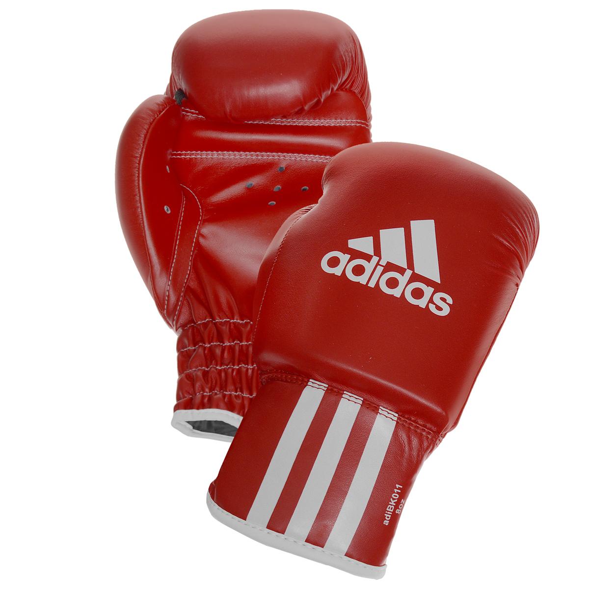Перчатки боксерские Adidas Rookie-2, цвет: красный. adiBK011. Вес 8 унцийadiBK011Боксерские перчатки Adidas Rookie-2 изготовлены из мягкого полиуретана, который по своим качествам не уступает натуральной коже. Внутренний наполнитель из многослойной пены обеспечивет надежную защиту рук боксера и позволяя безопасно тренироваться в полную силу. Предварительно изогнутый крой перчатки позволяет боксеру держать кулак в правильном положении. Загнутый параллельно кулаку большой палец обеспечивает безопасность при нанесении ударов и защищает большой палец от вывихов и травм. Внутренняя подкладка и вентиляционные отверстия на ладони создают максимальный уровень комфорта для рук, поддерживая оптимальный микроклимат внутри перчаток.