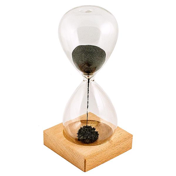 """Часы песочные Завораживающая иллюзия. 9521995219Оригинальные песочные часы Завораживающая иллюзия удивят и привлекут к себе внимание каждого. Внутрь стеклянной колбы помещен порошок из железа. На деревянной подставке под часами расположен магнит. При переворачивании часов железный """"песок"""" начинает притягиваться магнитом, создавая при этом причудливые формы. Часы необычного дизайна великолепно оформят интерьер и станут отличным сувениром для ценителей всего неординарного. Цикл песочных часов: 1 мин."""