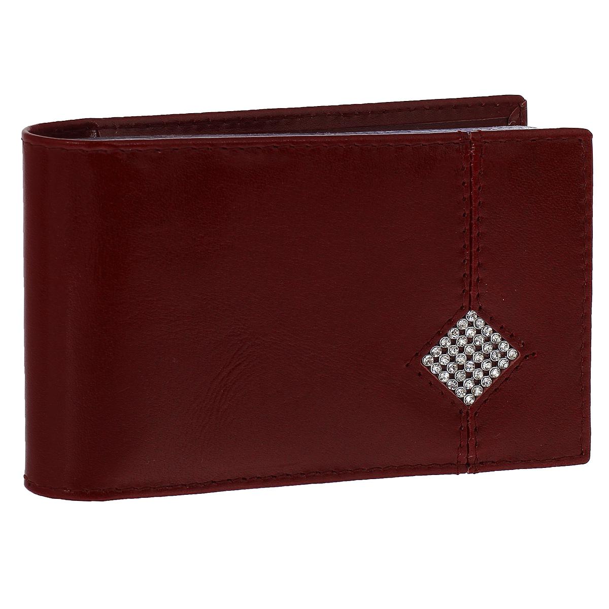 Футляр для визиток Dimanche Гранат, цвет: бордовый. 134134Футляр для визиток Dimanche Гранат изготовлен из высококачественной натуральной глянцевой кожи бордового цвета. Лицевая сторона обложки украшена стразами. Внутри содержится блок из прозрачных пластиковых файлов на 16 визиток, а также дополнительный карман для пластиковой карты. Стильный футляр эффектно дополнит ваш яркий образ и поможет хранить визитки и пластиковые карты в одном месте.