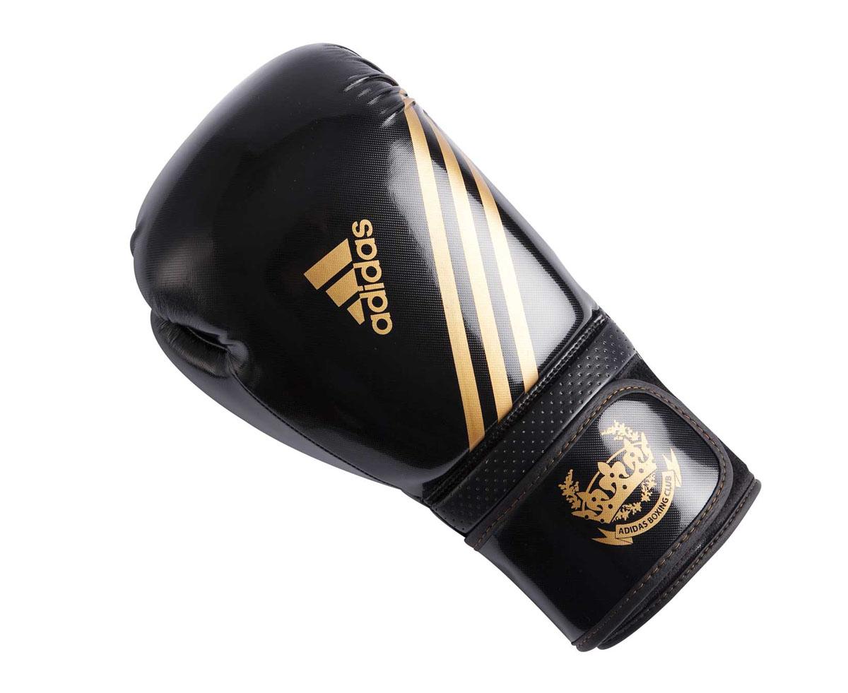 Перчатки боксерские Adidas Hybrid Aero Tech, цвет: черно-золотой. adiBL06. Вес 8 унцийadiBL06Боксерские перчатки Adidas Hybrid Aero Tech изготовлены из полиуретана PU4G, который по своим качествам не уступает натуральной коже. Внутренний наполнитель из многослойной пены закрывает тыльную сторону и боковую часть ладони, обеспечивая надежную защиту рук боксера и позволяя безопасно тренироваться в полную силу. Загнутый параллельно кулаку большой палец обеспечивает безопасность при нанесении ударов и защищает большой палец от вывихов и травм. Вентиляционные отверстия на ладони создают максимальный уровень комфорта для рук, поддерживая оптимальный микроклимат внутри перчаток. Широкий ремень, охватывая запястье, полностью оборачивается вокруг манжеты, благодаря чему создается дополнительная защита лучезапястного сустава от травмирования. Застежка на липучке способствует быстрому и удобному одеванию перчаток, плотно фиксирует перчатки на руке.