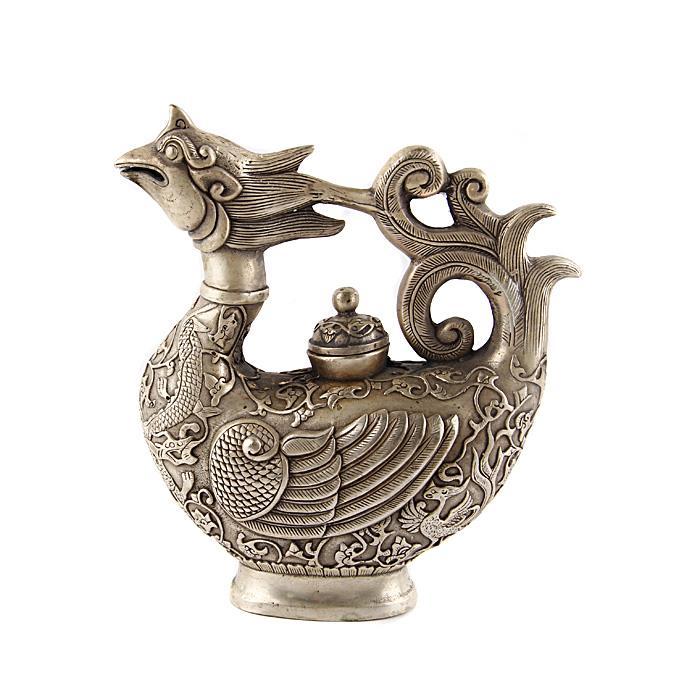 Чайник Чудо-птица в тибетском стиле. Металл, прочеканка. Китай, вторая половина XX века791504Чайник Чудо-птица в тибетском стиле. Металл, прочеканка. Китай, вторая половина XX века. Высота 19 см, длина 17 см, ширина 7 см. На дне иероглифическое клеймо. Сохранность хорошая. На Востоке особое значение имеют форма и цвет чайников и чайных сервизов. Оригинальный фигурный чайник из сплава серебристого цвета выполнен в виде прекрасной диковинной птицы. Оригинальный чайник в тибетском стиле станет прекрасным подарком любителям Востока и ярким элементом декора. Прекрасный образец декоративно-прикладного искусства Тибета, оригинальный подарок почитателю буддийской культуры.