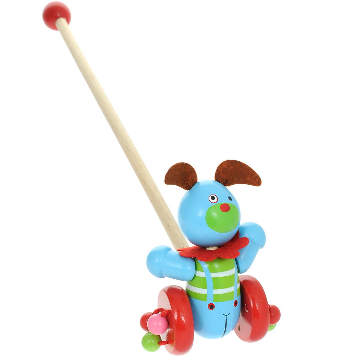 Mapacha Деревянная игрушка-каталка Веселый щенок76425Яркая игрушка-каталка Mapacha Веселый щенок непременно понравится вашему малышу и подойдет для игры как дома, так и на свежем воздухе. Яркая игрушка выполнена из дерева в виде забавного щенка на колесиках. Головка щенка подвижна, передние лапки прикреплены к туловищу эластичной резинкой. К колесикам игрушки с помощью текстильных шнурочков крепятся разноцветные деревянные шарики, которые гремят во время движения. Ручку-держатель можно открутить и играть только с игрушкой. В целях безопасности ручка дополнена круглым набалдашником. Игрушка-каталка Mapacha Веселый щенок способствует физическому развитию малыша - помогает сделать первые шаги и освоить навыки ходьбы. Развивает координацию движений и способность ориентироваться в пространстве.