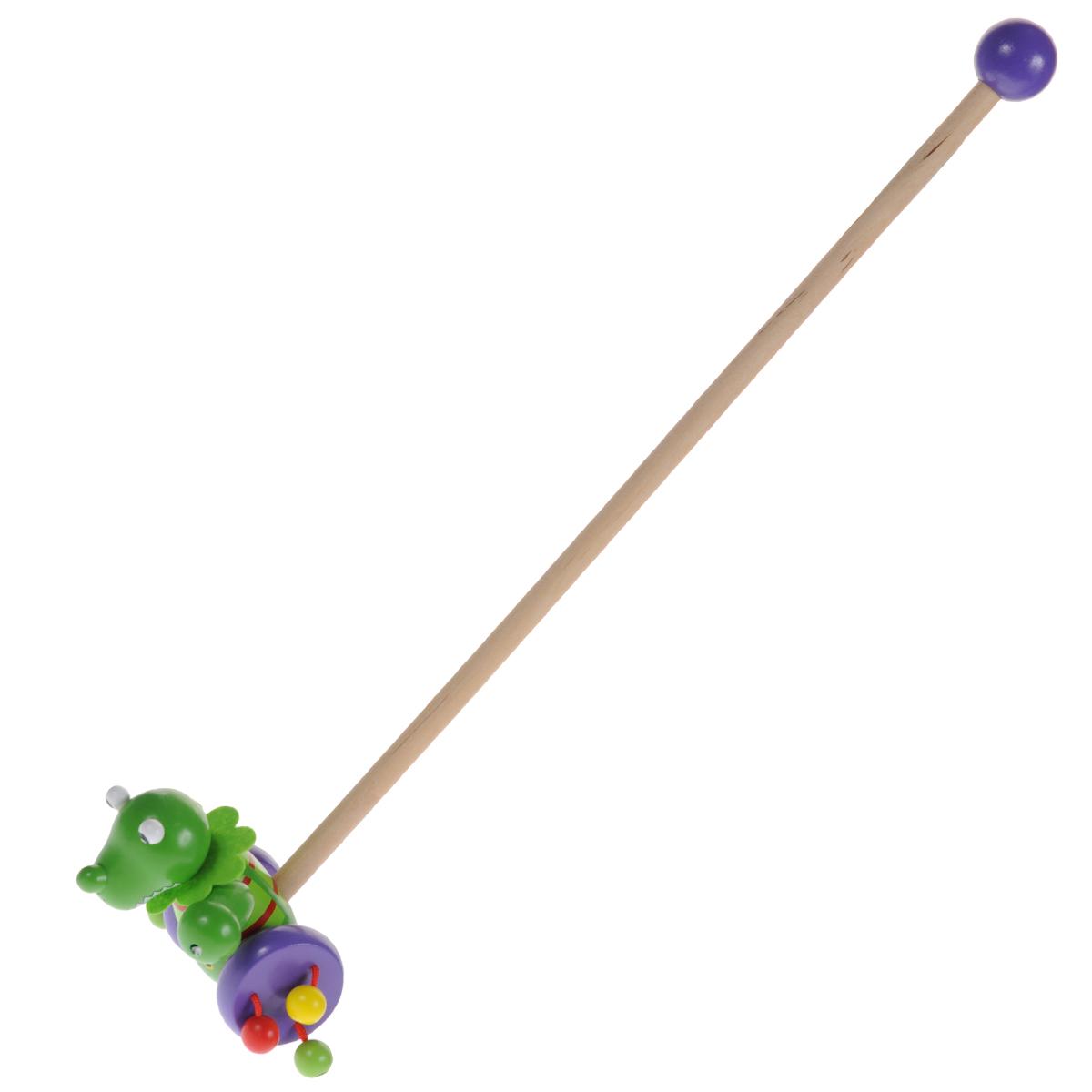 Mapacha Деревянная игрушка-каталка Динозаврик76424Яркая игрушка-каталка Mapacha Динозаврик непременно понравится вашему малышу и подойдет для игры как дома, так и на свежем воздухе. Яркая игрушка выполнена из дерева в виде динозаврика на колесиках. Головка динозаврика подвижна, передние лапки прикреплены к туловищу эластичной резинкой. К колесикам игрушки с помощью текстильных шнурочков крепятся разноцветные деревянные шарики, которые гремят во время движения. Ручку-держатель можно открутить и играть только с игрушкой. В целях безопасности ручка дополнена круглым набалдашником. Игрушка-каталка Mapacha Динозаврик способствует физическому развитию малыша - помогает сделать первые шаги и освоить навыки ходьбы. Развивает координацию движений и способность ориентироваться в пространстве.