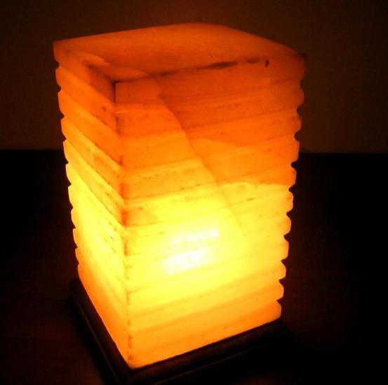 Лампа солевая Wonder Life Пятый элемент474Лампа солевая Wonder Life Пятый элемент изготовлена из природной каменной соли. Материал плафона лампы - натуральная гималайская соль из Пакистана. Соль в холодном состоянии обладает способностью поглощать влагу из воздуха, а при нагреве выделять влагу. Источником света в лампе служит электрическая лампочка (входит в комплект). Лампа имеет деревянную подставку. Солевая лампа станет не только прекрасным элементом интерьера, но и мягким природным ионизатором, который принесет в ваш дом красоту, гармонию и здоровье. Преимущества очищения воздуха каменной солью: облегчение головной боли при мигрени, повышение уровня серотонина в крови, уменьшение тяжести приступов астмы, укрепление иммунной системы и снижение уязвимости к простуде и гриппу. Количество граней может отличаться от картинки и в зависимости от свойств камня варьироваться от 7 до 11 граней. В целях безопасности включенную лампу ничем нельзя накрывать.