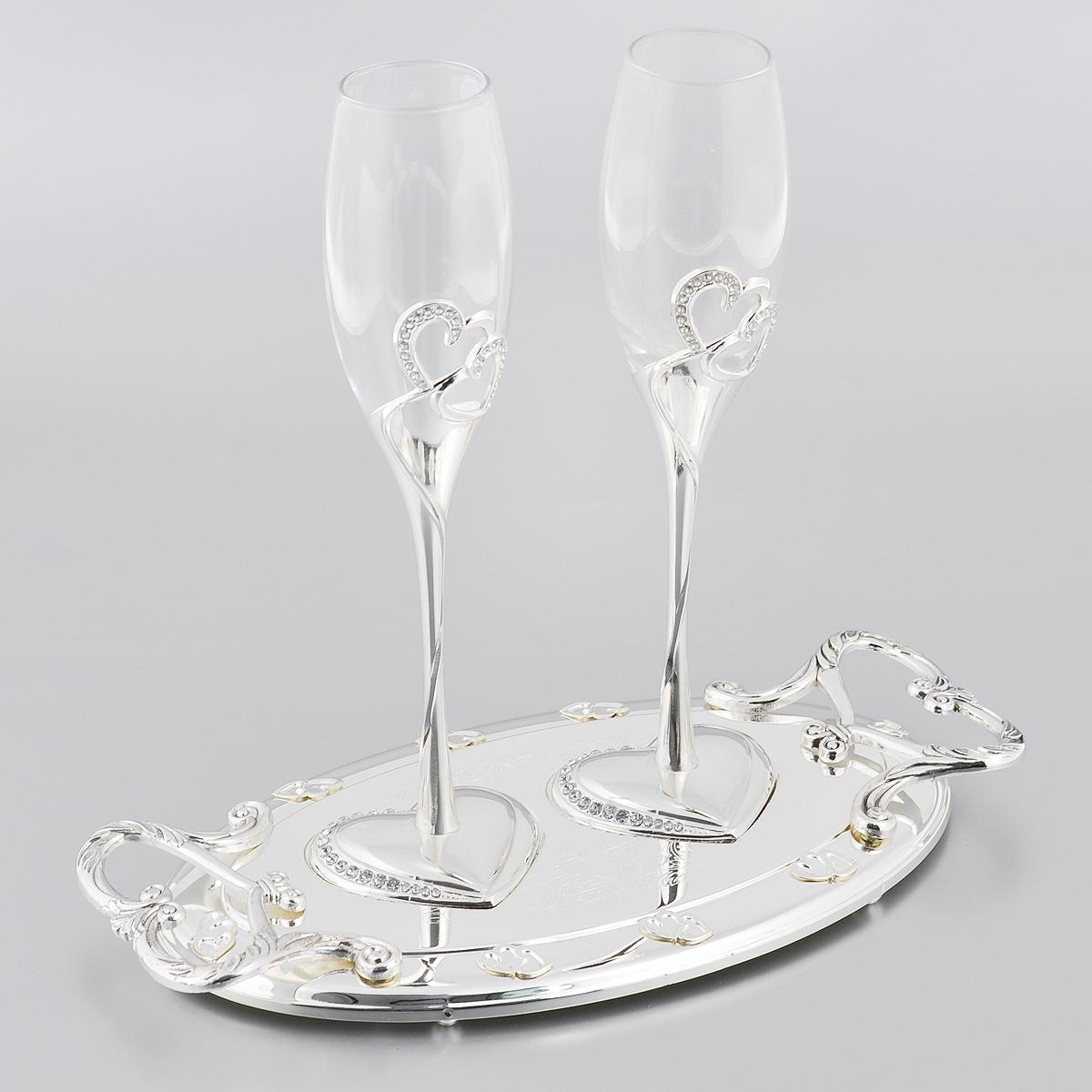 Набор бокалов Marquis Свадьба, на подносе, цвет: серебристый, 3 предмета2017-MRНабор Marquis Свадьба состоит из двух бокалов для шампанского для молодоженов и подноса. Бокалы выполнены из стекла. Изящные тонкие ножки, выполненные из стали с серебряно-никелевым покрытием, оформлены перфорацией в виде двух сплетенных сердец, инкрустированных стразами. Основание в виде сердца также оформлено стразами. Овальная подставка с ручками, украшенная гравировкой и рельефом, прекрасно дополняет набор. Такой набор принесет особую атмосферу торжества и праздника.