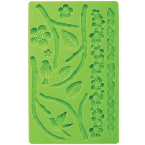 Молд для нанесения рисунка на мастику Wilton Природа, цвет: зеленый, 20 см х 12,5 смWLT-409-2Молд для нанесения рисунка на мастику Wilton Природа, выполненный из силикона, поможет вам легко нанести рисунки на мастику и сахарную пасту для тортов и сладких угощений. Молд содержит формы в виде цветов, веток и листьев. Использование и хранение: Перед первым использованием и после каждого применения вымойте молд в мыльной воде или на верхней полке в посудомоечной машине. Хорошо высушите молд перед использованием. Полезные советы по использованию: - Для того, чтобы мастика или цветочная паста не прилипали к молду, посыпьте его сахарной пудрой или смажьте растительным жиром сахарную мастику прежде чем накладывать на нее молд, - При раскатывании сахарной мастики используйте скалку для того, чтобы вся мастика была в полостях молда, - Следуйте инструкциям по изготовлению украшений, разместите их на торте, высушите. Изготовление: Скатайте сахарную мастику в трубочку такого же размера, как и полость молда. Положите...