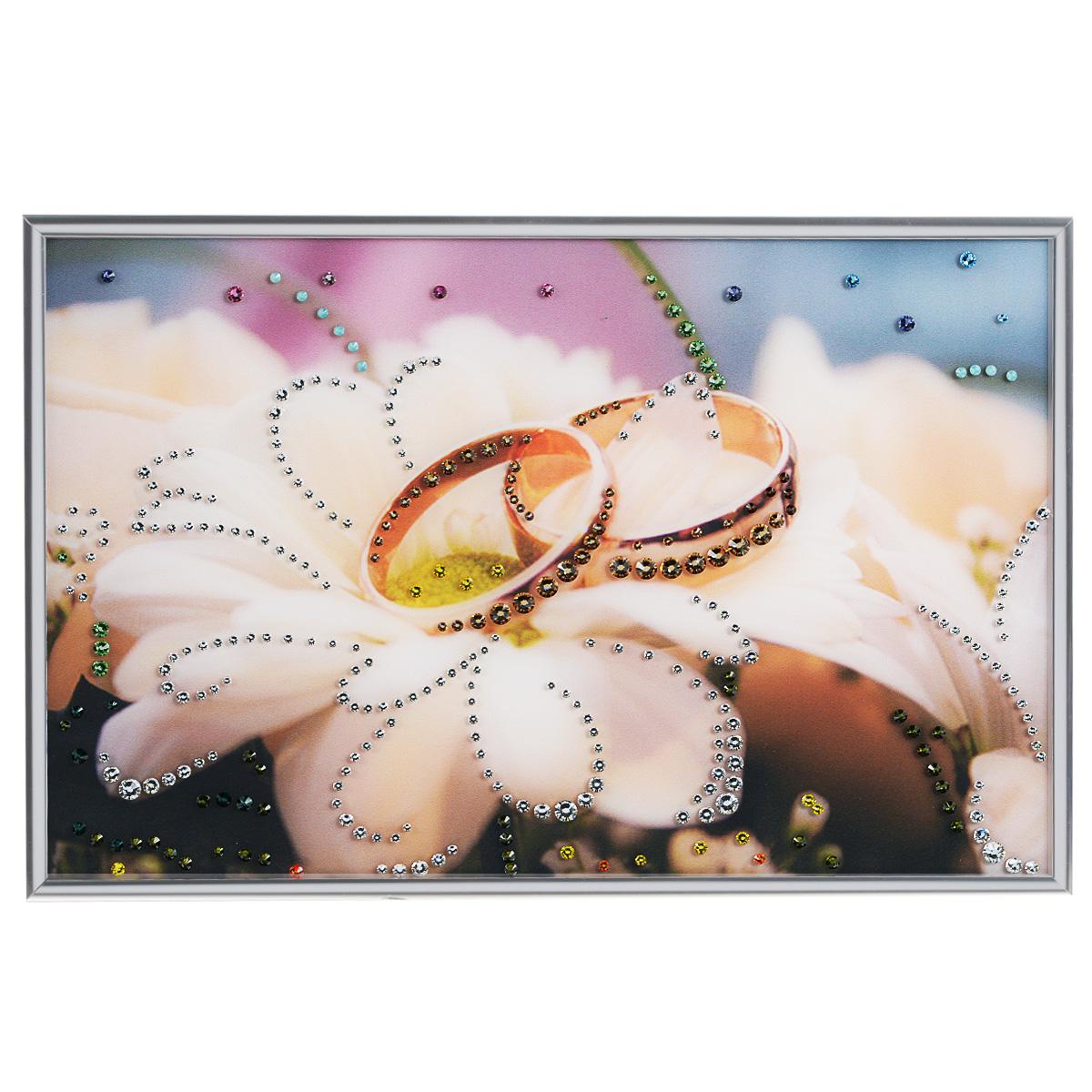 Картина с кристаллами Swarovski Обручальное кольцо, 30 х 20 см1231Изящная картина в металлической раме, инкрустирована кристаллами Swarovski, которые отличаются четкой и ровной огранкой, ярким блеском и чистотой цвета. Красочное изображение обручальных колец, расположенное под стеклом, прекрасно дополняет блеск кристаллов. С обратной стороны имеется металлическая петелька для размещения картины на стене. Картина с кристаллами Swarovski Обручальное кольцо элегантно украсит интерьер дома или офиса, а также станет прекрасным подарком, который обязательно понравится получателю. Блеск кристаллов в интерьере, что может быть сказочнее и удивительнее. Картина упакована в подарочную картонную коробку синего цвета и комплектуется сертификатом соответствия Swarovski.