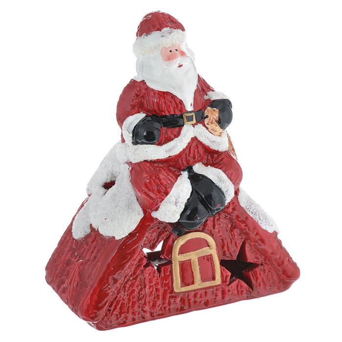 Новогодний декоративный подсвечник House & Holder Дед Мороз, цвет: красный. DJD1T023DJD1T023Новогодний декоративный подсвечник House & Holder Дед Мороз, выполненный из керамики и декорированный блестками, украсит интерьер вашего дома или офиса в преддверии Нового года. Оригинальный дизайн и красочное исполнение создадут праздничное настроение. Подсвечник выполнен в виде Деда Мороза, сидящего на заснеженной крыше дома. С оборотной стороны подсвечника есть отверстие, куда вставляется свеча. По всей поверхности расположены небольшие отверстия, через которые свет свечи будет проникать наружу, и озарять собой все вокруг. Вы можете поставить подсвечник в любом месте, где он будет удачно смотреться, и радовать глаз. Кроме того - это отличный вариант подарка для ваших близких и друзей.
