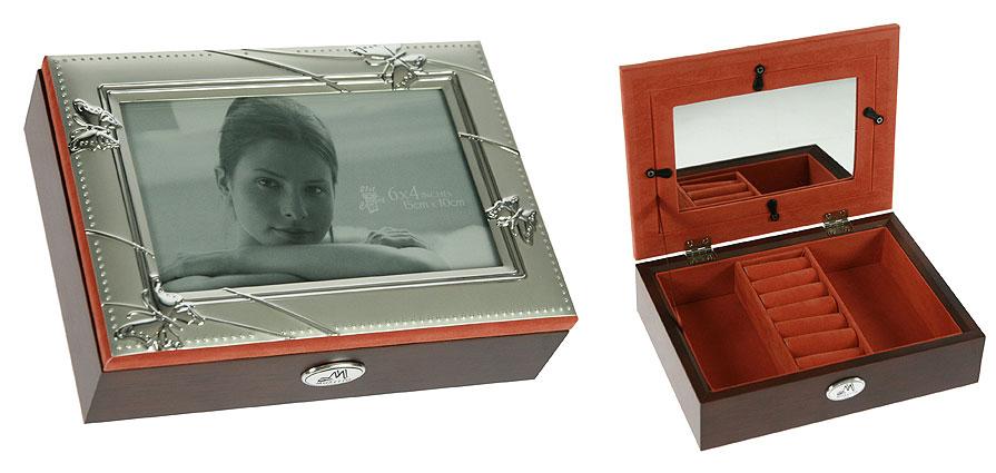 Шкатулка-фоторамка ювелирная Moretto, 19 х 14 х 5,5 см 139527139527Шкатулка-фоторамка Moretto изготовлена из МДФ коричневого цвета и предназначена для хранения ювелирных украшений. По периметру крышка оформлена алюминиевой гравюрой с изображением бабочек, в центр которой под стекло вы можете поместить фотографию размером 10 см х 15 см. Внутренняя поверхность шкатулки отделана бархатистой тканью кирпичного цвета. Изделие имеет два прямоугольных отделения для цепочек и браслетов и отсек с валиками для колец. Крышка с внутренней стороны оснащена прямоугольным зеркальцем. Шкатулка на передней стенке оснащена изящной эмблемой бренда. Шкатулка-фоторамка Moretto станет чудесным аксессуаром для хранения ювелирных украшений. Размер шкатулки: 19 см х 14 см х 5,5 см.