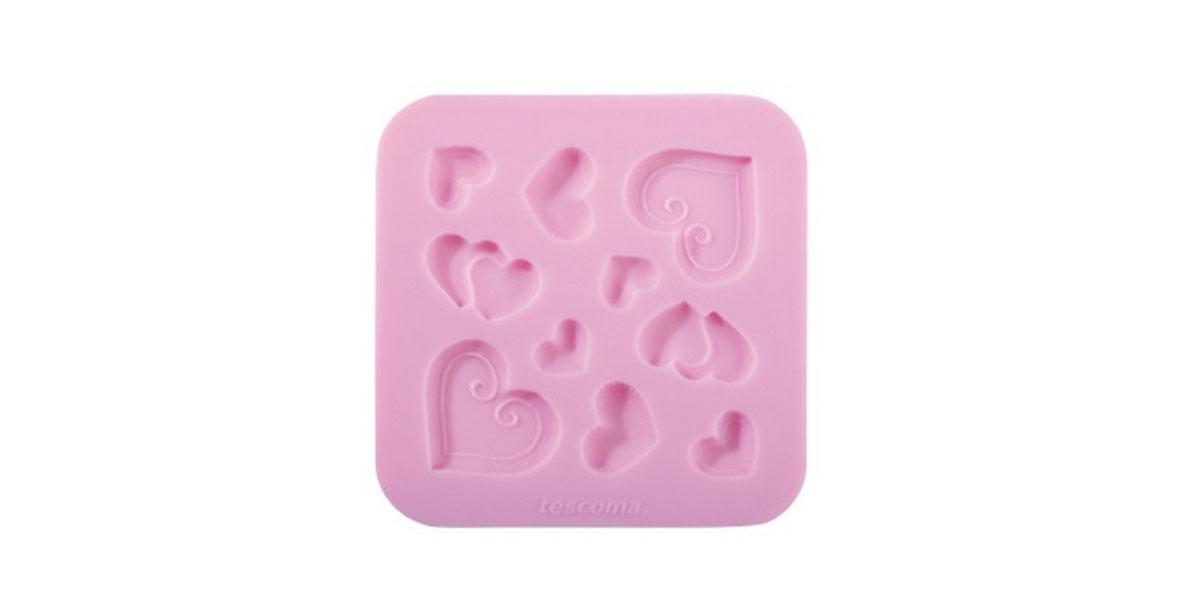 Форма для украшения выпечки Tescoma Сердечки, 10 ячеек633020Форма Tescoma Сердечки отлично подходит для украшения выпечки фигурками из марципана или помадки. Необходимо поставить заполненные формы в морозильник на 5-10 минут, а затем вытащить их, мягко нажав на дно формы. Форма изготовлена из превосходного гибкого силикона. На одном листе расположены 10 ячеек в форме сердечек. Можно мыть в посудомоечной машине.