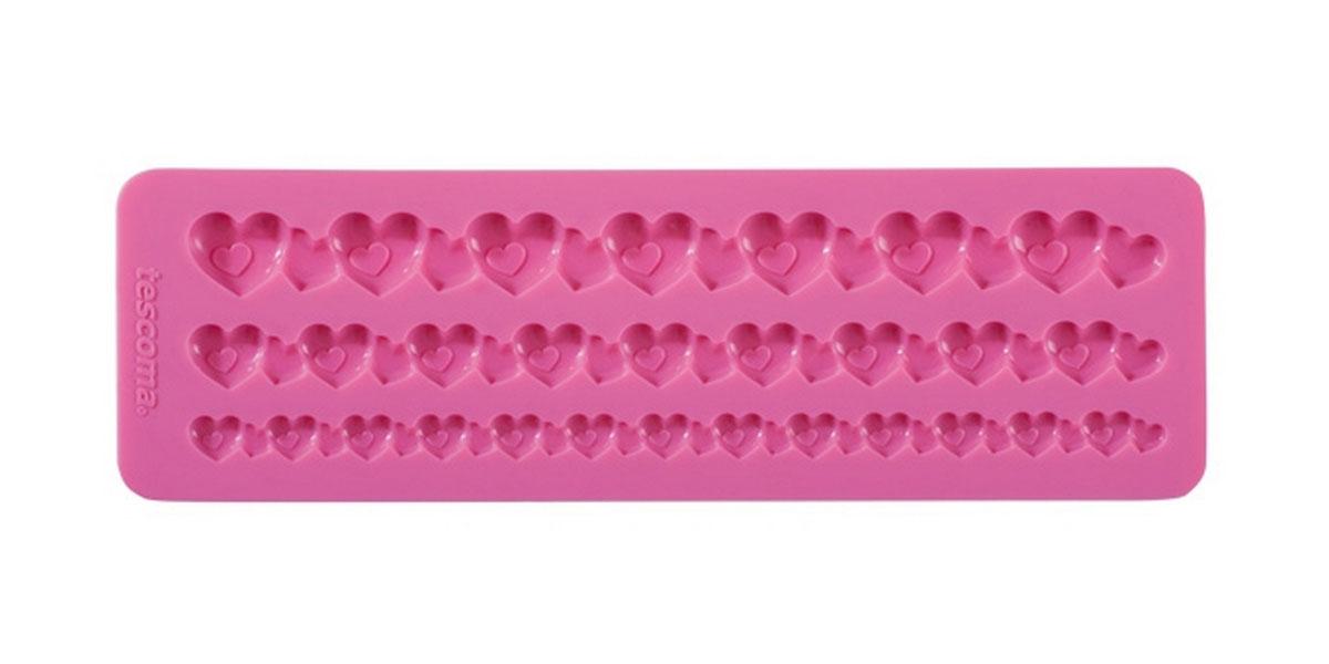 Форма для украшения выпечки Tescoma Бордюр с сердечками, 3 ячейки633040Форма Tescoma Бордюр с сердечками отлично подходит для украшения выпечки фигурками из марципана или помадки. Необходимо поставить заполненные формы в морозильник на 5-10 минут, а затем вытащить их, мягко нажав на дно формы. Форма изготовлена из превосходного гибкого силикона. На одном листе расположены 3 ячейки в виде полосок из сплетенных сердечек разных размеров. Можно мыть в посудомоечной машине.