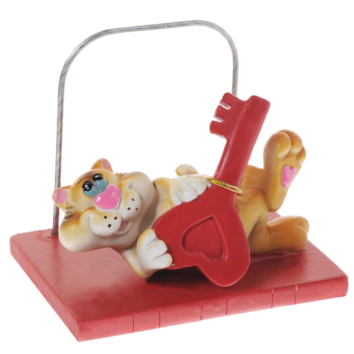 Статуэтка декоративная Home Queen Кот, с подставкой для телефона, цвет: красный, оранжевый64069Очаровательная статуэтка Home Queen Кот станет оригинальным подарком для всех любителей стильных вещей. Она выполнена из полирезины в виде кота с ключом и имеет удобную поставку под телефон. Изысканный сувенир станет прекрасным дополнением к интерьеру. Вы можете поставить статуэтку в любом месте, где она будет удачно смотреться, и радовать глаз.