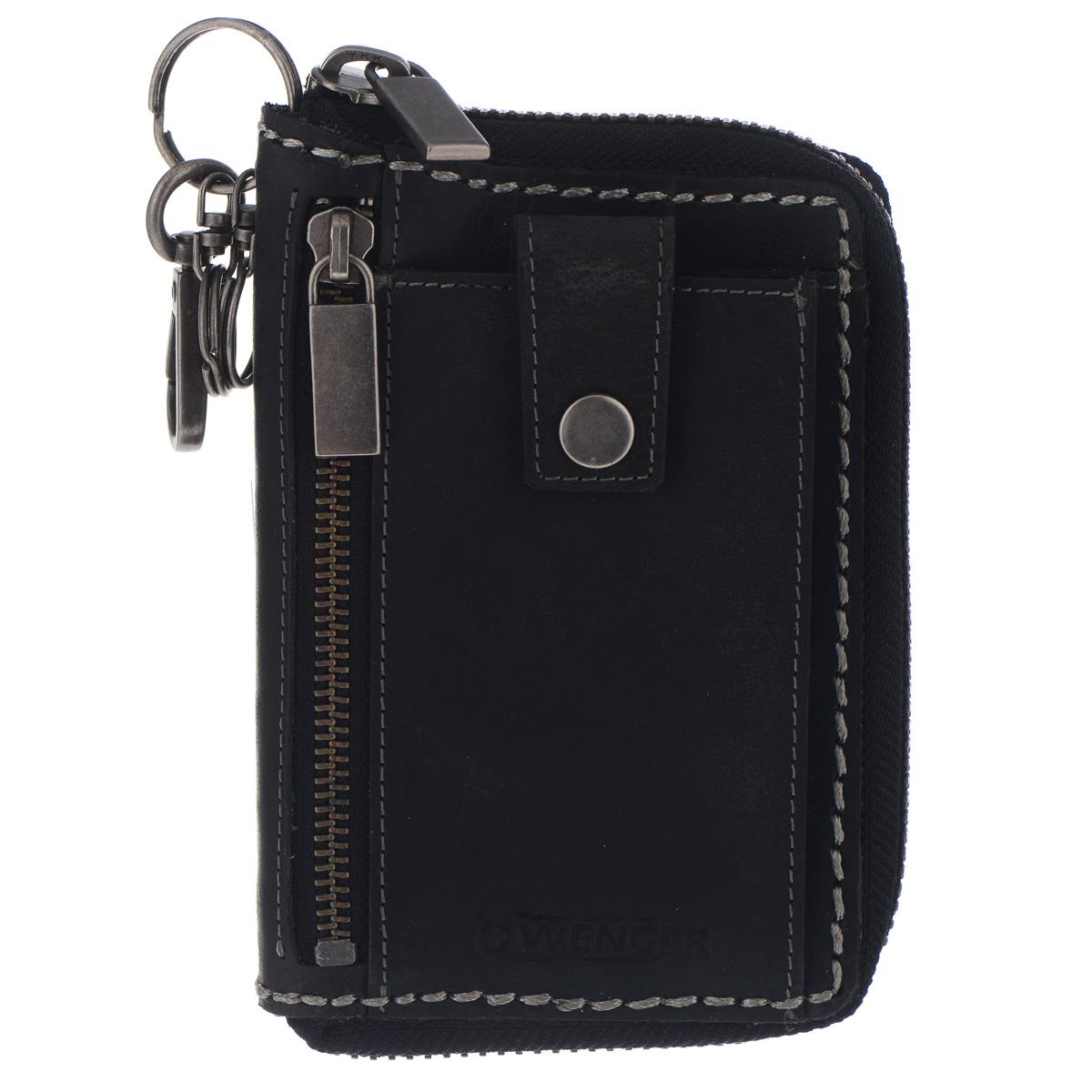 Портмоне мужское Wenger, цвет: черный. W23-21W23-21BLACKОригинальное мужское портмоне Wenger изготовлено из натуральной кожи и оформлено крупными декоративными стежками, фирменным тиснением на лицевой и обратной сторонах. Внутреннее отделение, закрывающееся на застежку-молнию, содержит один отсек для бумаг и чеков, четыре прорези для визиток и кредитных карт и два сетчатых кармана для фото. На задней стенке портмоне расположен отсек на кнопках, который дополнен пятью прорезями, двумя сетчатыми карманами, держателем для письменных принадлежностей и четырьмя кармашками для SIM-карт и флеш-карт. На лицевой стороне расположен отсек для мелочи на застежке-молнии и накладной карман для мобильного телефона на замке-кнопке, на обратной - открытый карман. Изделие оснащено тремя металлическими кольцами и карабином для хранения ключей. Портмоне упаковано в фирменную коробку. Модное портмоне Wenger займет достойное место среди вашей коллекции аксессуаров.