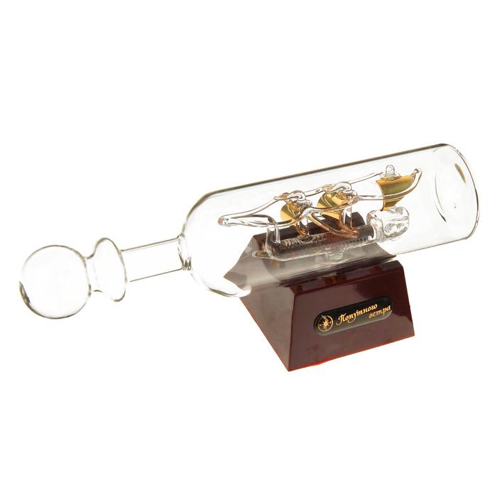 Корабль сувенирный в бутылке Попутного ветра, с подсветкой, длина 20 см. 454600454600Сувенирный корабль в бутылке Попутного ветра - великолепный элемент декора рабочей зоны в офисе или кабинете. В прозрачную бутылку помещена фигурка трехмачтового корабля с золотыми парусами. Для бутылки предусмотрена пластиковая подставка, украшенная надписью Попутного ветра. Стремящиеся в неизведанную даль, словно невесомые паруса заиграют по-новому, если вы включите яркую подсветку. Время идет, и мы становимся свидетелями развития технического прогресса, новых учений и практик. Но одно не подвластно времени - это любовь человека к морю и кораблям. Сувенирный корабль в бутылке наполнен историей и силой океанских вод. Данная модель кораблика станет отличным подарком для всех любителей морей, поклонников историй о покорении океанов и неизведанных земель. Модель корабля - подарок со смыслом. Издавна на Руси считалось, что корабли приносят удачу и везение. Поэтому их изображения, фигурки и точные копии всегда присутствовали в помещениях. Удивите себя и...