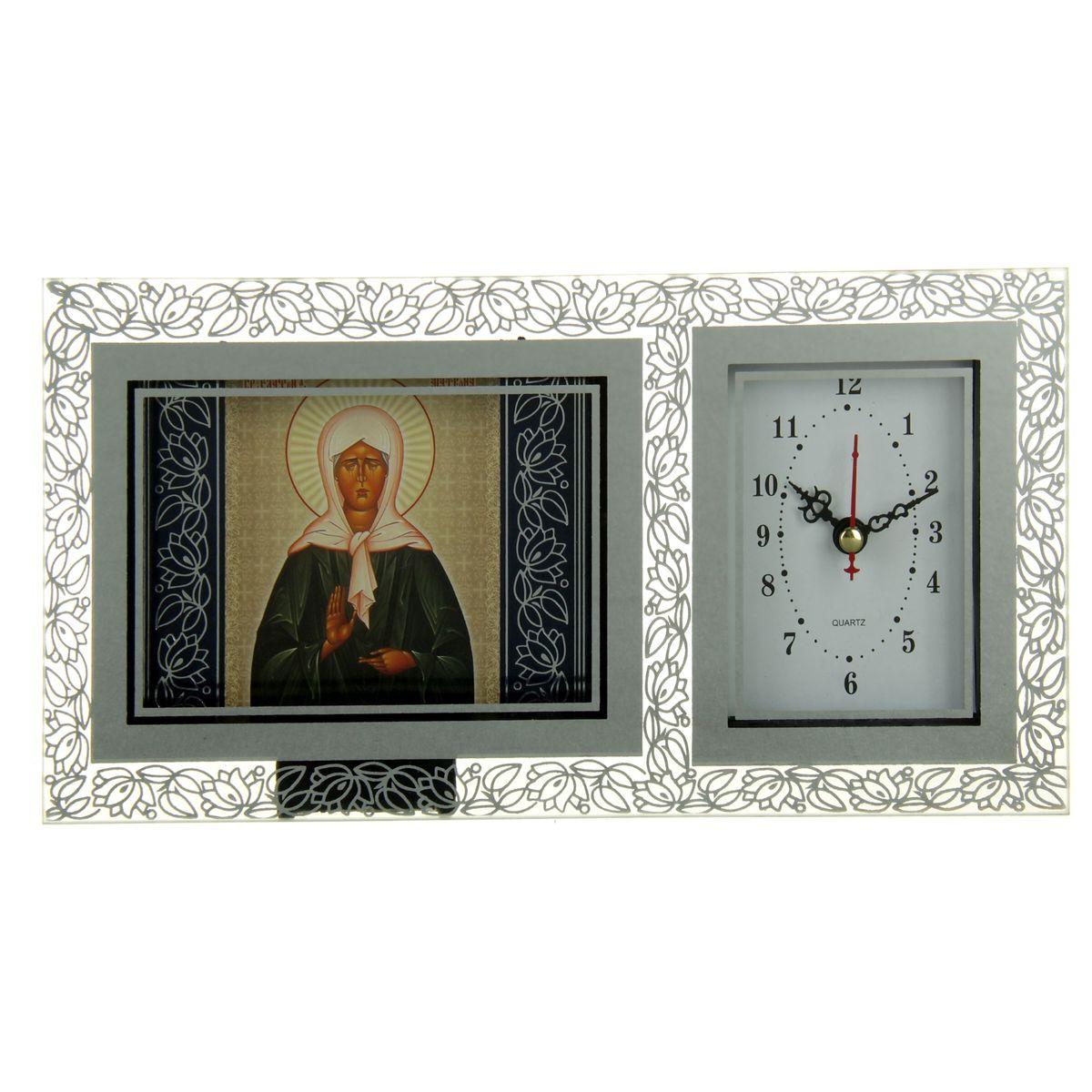 Часы с иконой Блаженная Матрона Московская, 26 см х 13 см157232Часы с иконой Блаженная Матрона Московская помогут красиво оформить интерьер вашего дома. Изделие выполнено из прозрачного стекла, украшено цветочным узором и зеркальным покрытием вокруг иконы и часов. Часы имеют прямоугольный циферблат белого цвета, 3 фигурные стрелки показывают часы, минуты и секунды. Часы устанавливаются на любую плоскую поверхность, стол или полку. Любое помещение выглядит незавершенным без правильно расположенных предметов интерьера. Они помогают создать уют, расставить акценты, подчеркнуть достоинства или скрыть недостатки. Не бывает незначительных деталей. Из мелочей складывается образ человека и стиль интерьера. Часы с иконой - одна из тех деталей, которые придают дому обжитой вид и создают ощущение уюта. Часы работают от одной батарейки типа АА.
