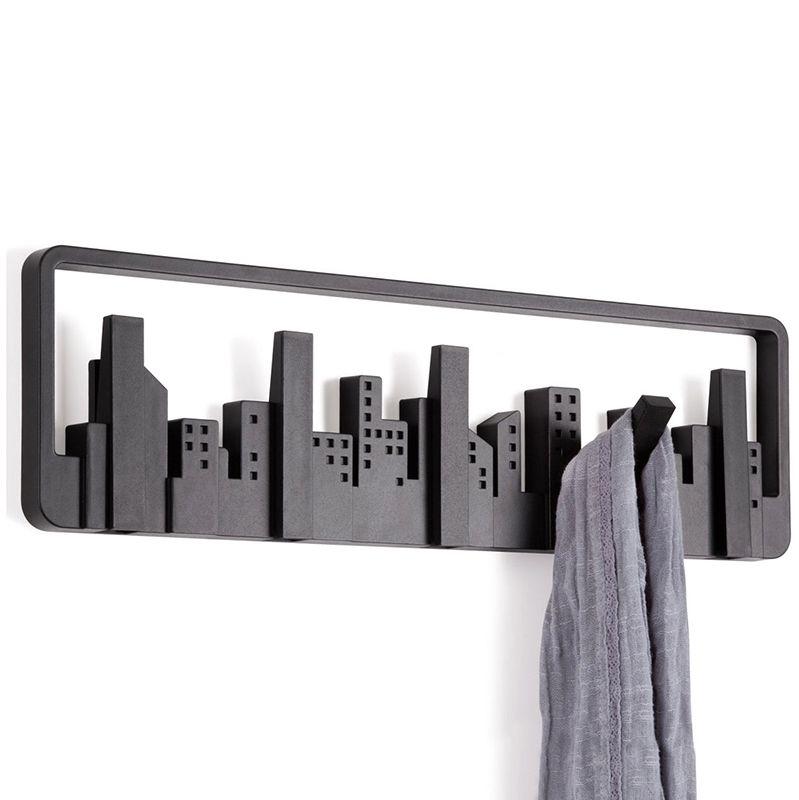 Вешалка настенная Umbra Skyline, цвет: черный, 5 крючков318190-040Силуэт оригинальной вешалки Umbra Skyline всем знаком: открывающийся из окна вид на мегаполис. В череде разновысотных домов-параллелепипедов можно увидеть пять самых высоких небоскребов - они представляют собой замаскированные крючки для одежды. При необходимости крючки откидываются и используются по назначению. Каждый крючок выполнен из прочного пластика и выдерживает нагрузку до 2,3 кг. Вешалка Umbra Skyline идеально подходит для маленьких прихожих и ограниченных пространств. Размер вешалки: 50 см х 14 см х 1,5 см.