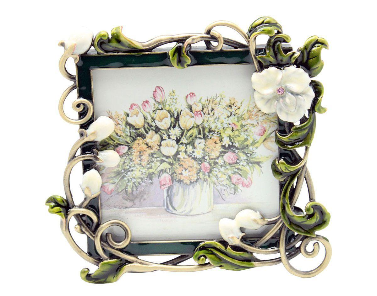 Рамка для фотографий Jardin DEte Белые цветы, 10 х 10 см HS-25011CHS-25011CИзящная рамка для фотографий Jardin DEte Белые цветы выполнена из сплава олова, покрытого эпоксидной смолой. С задней стороны имеется ножка для удобного размещения. Такая рамка позволит хранить на самом видном месте фотографию ваших родных и близких, а также великолепно украсит интерьер помещения.