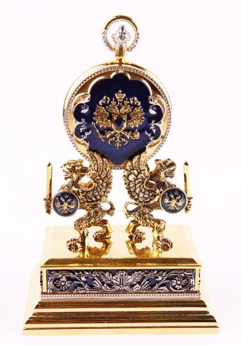 Набор Имперский из 2-х предметов: часы карманные + пресс-папье. Металл, эмаль гильош, позолота, австрийские кристаллы. Фаберже, The Franklin Mint, 1990-е гг.GBA-400-1A9Набор Имперский из 2-х предметов: часы карманные + пресс-папье. Металл, эмаль гильош, позолота, австрийские кристаллы. Фаберже, The Franklin Mint, 1990-е гг. Размеры: Часы: 5 х 7 см; Пресс-папье: 9,5 х 6,5 х 8,5 см. Сохранность очень хорошая. На основании пресс-папье и внутренней стороне часов - тисненые клейма House of Faberge; название The Imperial Collector Watch, TFM. Набор состоит из пресс-папье и позолоченных карманных часов, с гербом Российской Империи. Великолепные карманные часы от Фаберже - эталон превосходного сочетания хорошего вкуса и традиционного стиля Фаберже! Часы покрыты позолотой, украшены эмалью гильош и австрийскими кристаллами. Открытый механизм. На крышке часов - герб Российской Империи, в центре рельефа - синий кристалл. Прямоугольное основание пресс-папье создано в виде постамента, украшено ажурным рельефом. Верхняя часть изделия декорирована фигурными изображениями крылатых грифонов с мечами и щитами, на...