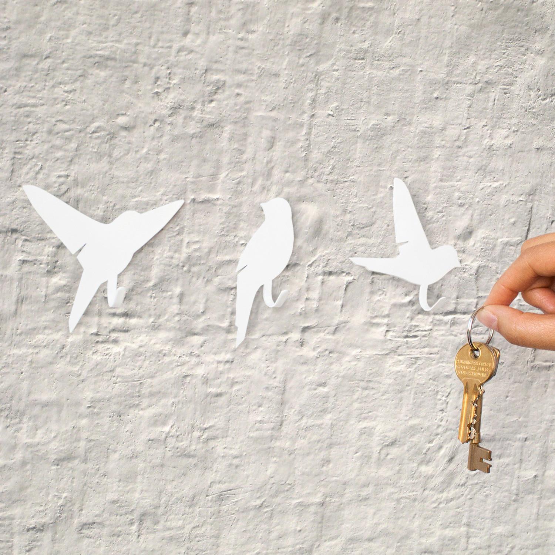Набор вешалок Suck UK Bird, цвет: белый, 3 штSK BIRDHOOKS1Набор Suck UK Bird состоит из трех вешалок, выполненных из металла в виде птичек. Изделия идеальны для хранения ключей, собачьих поводков, кухонных полотенец и других домашних предметов. Прекрасно смотрятся втроем, но можно использовать и по отдельности. Задняя сторона изделий клейкая, они легко крепятся к любой ровной сухой поверхности. Упакованы в красивую упаковку и станут идеальным подарком на новоселье. Размер вешалок: 7,5 см х 8 см; 3,5 см х 8 см; 8,5 см х 8 см.