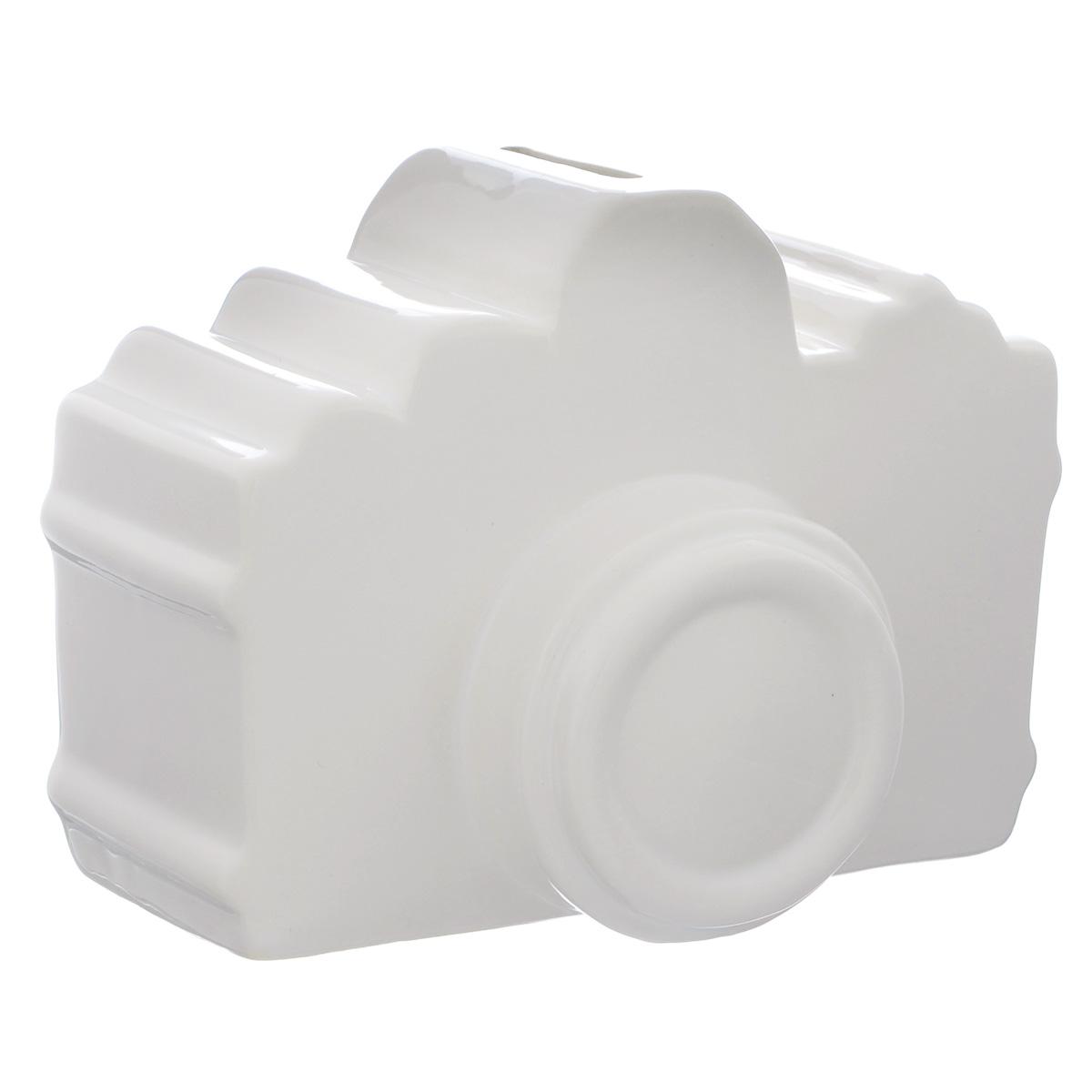 Копилка декоративная Фотоаппарат, цвет: белый36448Декоративная копилка Фотоаппарат изготовлена из доломитовой керамики. Яркий оригинальный дизайн сделает такую копилку прекрасным подарком. Она послужит не только по своему прямому назначению, но и красиво дополнит интерьер комнаты.