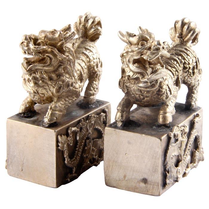 Настольный парный декор Львы-стражи. Металл, прочеканка. Китай. вторая половина XX векаПБ ДПА 16082016-8Настольный парный декор Львы-стражи. Металл, прочеканка. Китай. вторая половина XX века. Размеры 5 х 4 х 2 см. Сохранность хорошая. Дзиси, или львы-стражи располагаются парой по обеим сторонам. При этом, по правую руку обычно располагается лев, по левую — львица. Обычно лев придерживает лапой шар, который в буддийской традиции трактуется как тема — сокровище, символ буддийского знания, несущий свет во тьму и могущий исполнять желания. Львица придерживает лапой львёнка. Одна фигура с открытой пастью, другая — с закрытой. Это трактуется по-разному: как символ рождения и смерти; как символ открытости к добрым помыслам и неприятия злых. Вообще, открытая пасть должна отпугивать злых демонов, закрытая — удерживать и защищать добрых.