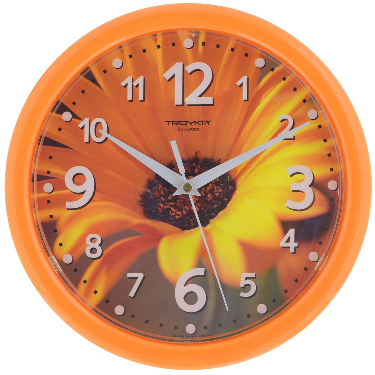Часы настенные Troyka Гербера, цвет: желтый, оранжевый. 2125122621251226Настенные кварцевые часы Troyka Гербера, изготовленные из пластика, прекрасно подойдут под интерьер вашего дома. Круглые часы имеют три стрелки: часовую, минутную и секундную, циферблат украшен изображением цветка герберы и защищен прозрачным пластиком. Диаметр часов: 24,5 см. Часы работают от 1 батарейки типа АА напряжением 1,5 В (входит в комплект).