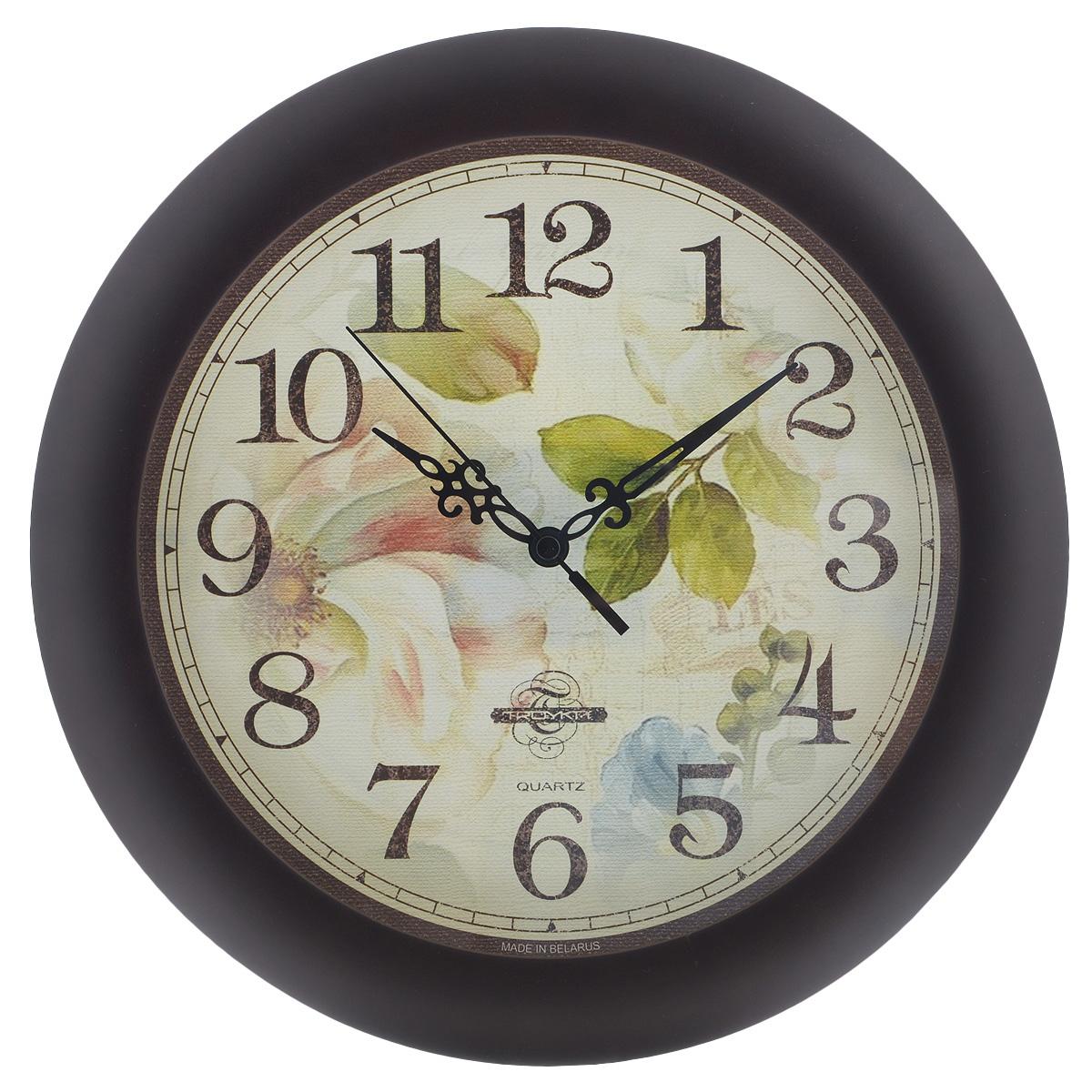 Часы настенные Troyka Цветы, цвет: светло-зеленый, коричневый. 1116315911163159Настенные кварцевые часы Troyka Цветы, изготовленные из пластика, прекрасно подойдут под интерьер вашего дома. Круглые часы имеют три стрелки: часовую, минутную и секундную, циферблат украшен изображением цветов и защищен прозрачным пластиком. Диаметр часов: 30 см. Часы работают от 1 батарейки типа АА напряжением 1,5 В (входит в комплект).
