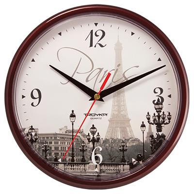 Часы настенные Troyka, цвет: коричневый. 9193192791931927Настенные кварцевые часы Troyka с изображением Эйфелевой башни, изготовленные из пластика, прекрасно подойдут под интерьер вашего дома. Круглые часы имеют три стрелки: часовую, минутную и секундную, циферблат защищен прозрачным пластиком. Диаметр часов: 22,5 см. Часы работают от 1 батарейки типа АА напряжением 1,5 В. Внимание! Часы укомплектованы бесплатным тестовым элементом питания для обеспечения их работоспособности при предпродажной подготовке и демонстрации рабочих функций.