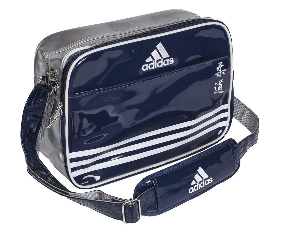 Сумка спортивная Adidas Sports Carry Bag Judo, цвет: синий, серебристый, белый. Размер SadiACC110CS2S-JСпортивная сумка Adidas Sports Carry Bag Judo изготовлена из искусственной кожи. На передней стороне сумки вышиты иероглифы Judo. Она предназначена для переноски и хранения спортивного инвентаря и других нужных для занятия спортом предметов. Сумка состоит из 1 большого отделения и 2 внешних карманов. Имеет удобный плечевой ремень.