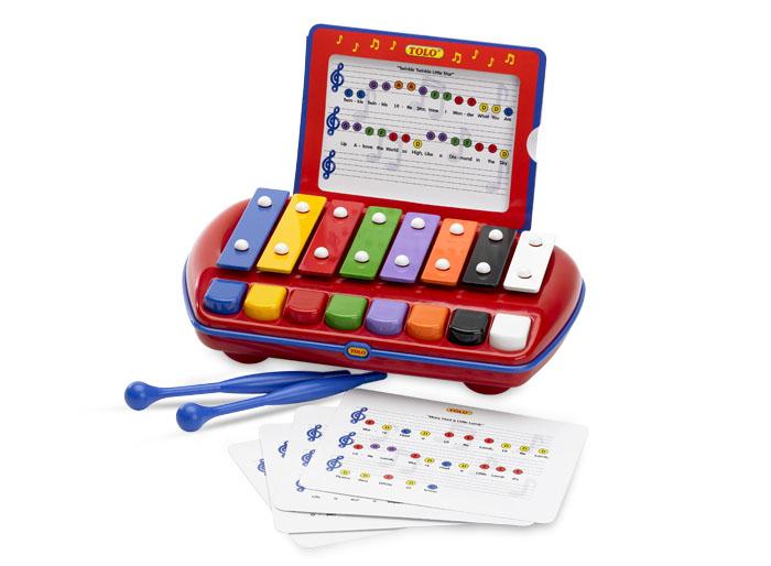 Tolo Classic Музыкальный инструмент Ксилофон89652Ксилофон Tolo toys - это ряд металлических пластин разной величины и цвета, настроенных на определенные ноты. Для игры на нём используются две палочки, похожие на барабанные. В комплекте малыш найдет 8 листов с нотками мелодий. Крохе нужно будет только ударять по пластине того цвета, который изображен на ноте. Если малыш еще не уверенно держит палочки в руках, кнопочки придут ему на помощь. Так - даже самые маленькие музыканты смогут проявить себя, ведь кнопки соответствуют пластинам того же цвета. На корпусе есть удобная ручка, которая позволит носить ксилофон с собой. Две палочки закрепляются на задней стенке ксилофона. Игра развивает мелкую моторику, логику, причинно-следственные связи, воображение, понятие цвета и звука, чувство ритма и творческие способности. Эта яркая музыкальная игрушка подарит множество приятных моментов маленькому музыканту!