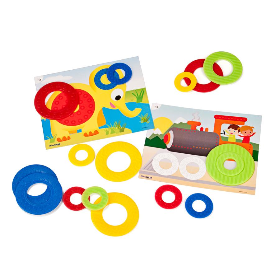 Miniland Обучающий набор Цветные кольца31796Комплект обучающих звеньев для развития навыков классификации и сортировки предметов по размерам, цветам, форме и текстуре, развития двигательно-моторной координации. Для выполнения упражнения нужно определить цвет и расположить кольца так, как указанно в заданиях В наборе 8 больших колец размером 9 см., 8 маленьких колец, 18 карточек с заданиями, методические указания для родителей и педагогов, кейс для сбора и хранения всех частей игры. Рекомендованный возраст 2-5 лет.