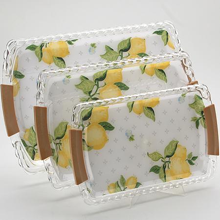 3249 Наб/подносов МВ 3пр Лимон накл/руч(х12)3249Набор подносов Лимон 3 предмета: Размер: 43х28х2,5 см 37х24х2,3 см 32х20х1,9 см Материал: пластик Размер упаковки: 43,5х28,5х4 см Вес: 900 г Набор Лимон состоит из трех прямоугольных подносов разного размера, выполненных из пластика. Подносы украшены изображением лимонов и оформлены изящным рельефным узором по краю. Они отлично подойдут для красивой сервировки различных блюд, закусок и фруктов на праздничном столе. Ручки подносов выполнены из пластмассы, оформленной под дерево. Набор подносов Лимон станет отличным подарком на любой праздник.