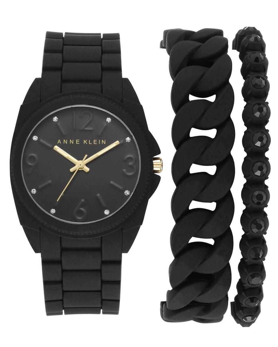 Подарочный набор Anne Klein: наручные часы, 2 браслета, цвет: черный. 1956BKST1956BKSTПодарочный набор Anne Klein включает в себя женские наручные часы и два браслета. Часы выполнены из металлического сплава, силикона и минерального стекла. Циферблат изделия инкрустирован стразами Swarovski и дополнен символикой бренда. Корпус часов оснащен кварцевым механизмом, имеет степень влагозащиты равную 3 atm, а также дополнен устойчивым к царапинам минеральным стеклом. Стрелки дополнены светящимся составом. Ремешок часов выполнен из силикона и оснащен замком-клипсой, который позволит с легкостью снимать и надевать изделие. Узкий браслет выполнен из силикона и металлического сплава и оформлен вставками со стразами Swarovski. Браслет застегивается на складной замочек, состоящий из двух звеньев, которые позволяют регулировать длину изделия. Минимальный обхват браслета - 21см. Широкий браслет выполнен в виде силиконовой цепочки. Минимальный обхват браслета - 21 см. Подарочный набор Anne Klein станет отличным сюрпризом для человека...