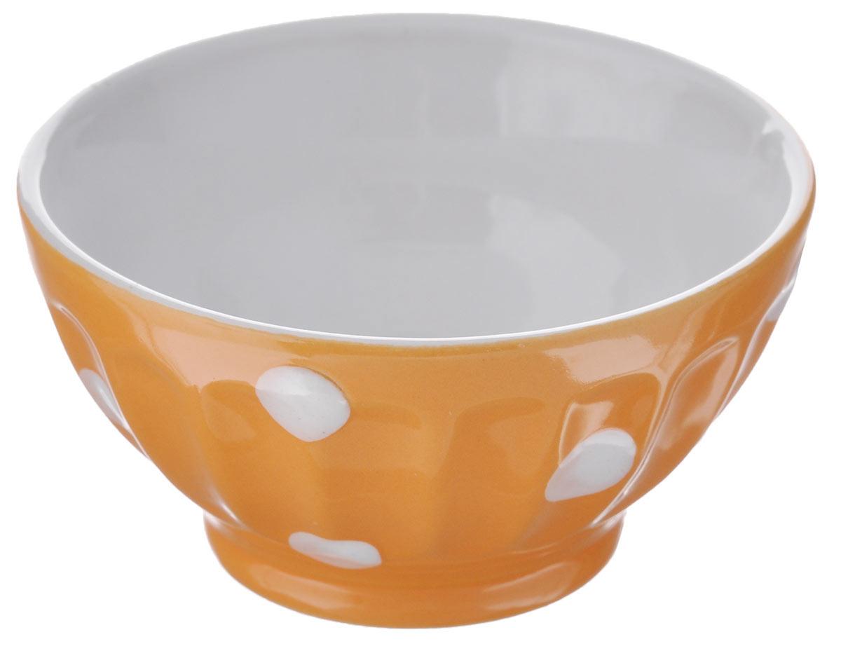 Салатница Kaiwei Веселый горошек, цвет: оранжевый, белый, 150 млLK1355-006OСалатница Kaiwei Веселый горошек изготовлена из высококачественной керамики и покрыта цветной глазурью, с выпуклыми на ощупь горохами и продольными гладкими ребрами. Глазурь - это кремнеземное стекло, которое, будучи расплавленным при очень высоких температурах в специальных печах для обжига изделий, создает на глине равномерную гладкую прозрачную поверхность. Именно благодаря ей пористая керамика обретает водонепроницаемость. Кроме того, глазурь предохраняет керамические изделия от загрязнения, действия кислот и щелочей и придаёт изделиям декоративные свойства. Объем: 150 мл. Диаметр салатницы по верхнему краю: 9 см. Высота стенки: 4,5 см. Можно использовать в СВЧ и посудомоечной машине.