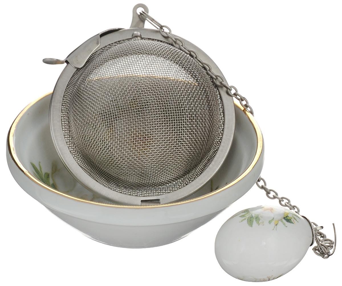 Ситечко для заваривания чая Elan Gallery Белый шиповник, с подставкой503552Ситечко для чая Elan Gallery Белый шиповник прекрасно подходит для заваривания любого вида чая. Ситечко выполнено из нержавеющей стали в форме шара, оно снабжено керамической подставкой и металлической цепочкой с фигуркой. Изделие очень легко использовать: просто засыпьте в ситечко заварку и опустите его в кружку. Подставка предотвращает образование подтеков на столе. Стильное и функциональное ситечко станет незаменимым атрибутом чаепития дома или на работе. Не использовать в микроволновой печи. Диаметр ситечка: 5 см. Диаметр подставки: 7 см. Высота подставки: 2,5 см. Длина цепочки: 12,5 см.